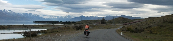 Guy Cycling Along Lake Pukaki with Mt Cook in the distance